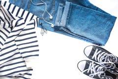 Μινιμαλιστική και μοντέρνη εξάρτηση - τζιν παντελόνι, μαύρα πάνινα παπούτσια, ριγωτά πουλόβερ και ακουστικά που απομονώνονται στο στοκ φωτογραφία με δικαίωμα ελεύθερης χρήσης
