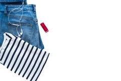 Μινιμαλιστική και μοντέρνη εξάρτηση - τζιν παντελόνι, ριγωτό πουλόβερ, κόκκινα στιλβωτική ουσία καρφιών και ακουστικά που απομονώ στοκ φωτογραφία