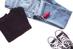 Μινιμαλιστική και μοντέρνη θηλυκή εξάρτηση - τζιν παντελόνι, μαύρα πάνινα παπούτσια, πουλόβερ, ακουστικά και κόκκινη στιλβωτική ο στοκ εικόνα