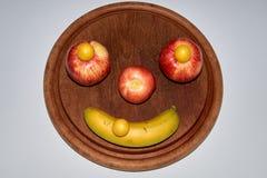 Μινιμαλιστικό στρογγυλό πρόσωπο φρούτων φιαγμένο από μήλο, ροδάκινο και μπανάνα στοκ εικόνα