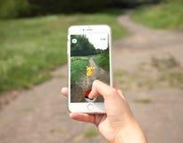 Μινσκ, Λευκορωσία - 28 Ιουλίου 2016: Η Apple iPhone6s που κρατιέται σε ένα χέρι που παρουσιάζει οθόνη της με Pokemon πηγαίνει εφα Στοκ Φωτογραφία