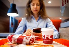 Μινσκ, Λευκορωσία, στις 21 Ιουλίου 2018: Φλυτζάνι σάντουιτς και εγγράφου στον πίνακα στο εστιατόριο της KFC Η γυναίκα πρόκειται ν Στοκ Εικόνες