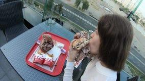 Μινσκ, Λευκορωσία, στις 2 Ιουνίου 2018: Η νέα γυναίκα δειπνεί στον πίνακα στο πεζούλι εστιατορίων της KFC με μια άποψη της πόλης απόθεμα βίντεο