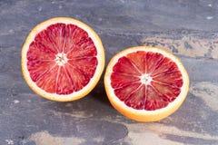 Μισά περικοπών ενός πορτοκαλιού αίματος στην γκρίζα πλάκα Στοκ Εικόνα