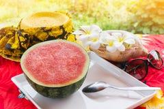 Μισά φρέσκα και κόκκινα φρούτα και κουτάλι καρπουζιών στον άσπρο δίσκο στο τ Στοκ φωτογραφίες με δικαίωμα ελεύθερης χρήσης