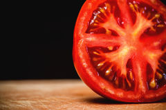 Μισή περικοπή που τεμαχίζεται της φρέσκιας ντομάτας στον ξύλινο πίνακα στοκ εικόνα