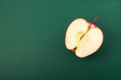 Μισή Apple, που απομονώνεται στο πράσινο υπόβαθρο Στοκ φωτογραφία με δικαίωμα ελεύθερης χρήσης