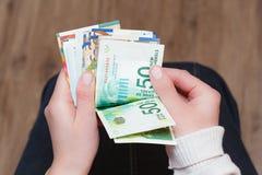 Μισθοί, μετρώντας χέρια της ισραηλινής Α γυναίκας χρημάτων Στοκ Εικόνες