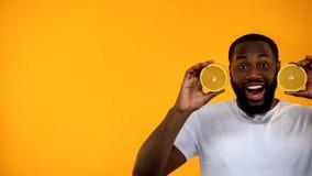 Μισό εκμετάλλευσης χαμόγελου αφροαμερικανός αρσενικό των πορτοκαλιών, υγιής διατροφή, πρότυπο στοκ εικόνες με δικαίωμα ελεύθερης χρήσης