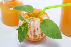 Μισό-καθαρισμένα πορτοκαλιά φρούτα με τα φύλλα μεντών, έννοια κοκτέιλ, σε γκρίζο Στοκ εικόνα με δικαίωμα ελεύθερης χρήσης