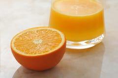 Μισό πορτοκάλι και ένα ποτήρι του πρόσφατα συμπιεσμένου χυμού από πορτοκάλι Στοκ φωτογραφία με δικαίωμα ελεύθερης χρήσης