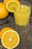 Μισό πορτοκάλι που βάζει εν πλω με το ποτήρι του ποτού χυμού από πορτοκάλι μέσα Στοκ Φωτογραφία