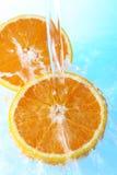 μισό πορτοκαλί ύδωρ παφλασμών Στοκ Εικόνες