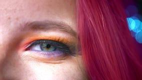 Μισό-πορτρέτο κινηματογραφήσεων σε πρώτο πλάνο της ρόδινος-μαλλιαρής θηλυκής ζωηρόχρωμης σύνθεσης ματιών στο θολωμένο μπλε υπόβαθ απόθεμα βίντεο