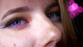 Μισό-πορτρέτο κινηματογραφήσεων σε πρώτο πλάνο του ξανθού θηλυκού με τα πορφυρά μάτια, της έξυπνης και ζωηρόχρωμης σύνθεσης στο ρ φιλμ μικρού μήκους