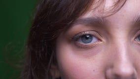 Μισό πορτρέτο προσώπου κινηματογραφήσεων σε πρώτο πλάνο της νέας προσοχής γυναικών σπουδαστών brunette με προσήλωση στη κάμερα στ απόθεμα βίντεο