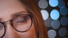 Μισό πορτρέτο προσώπου κινηματογραφήσεων σε πρώτο πλάνο του νέου αρκετά καυκάσιου κοριτσιού στα γυαλιά που εξετάζουν τη κάμερα κα φιλμ μικρού μήκους