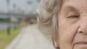 Μισό πρόσωπο της σοβαρής ηλικιωμένης γυναίκας υπαίθρια φιλμ μικρού μήκους