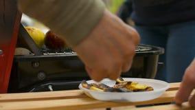 Μμένα τσιπ πατατών και μαγειρευμένη κινηματογράφηση σε πρώτο πλάνο μήλων κατά τη διάρκεια οικογενειακό BBQ της σχάρας έξω απόθεμα βίντεο
