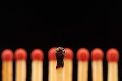 Μμένη αντιστοιχία μπροστά από οκτώ κόκκινες ξύλινες αντιστοιχίες Στοκ Φωτογραφία