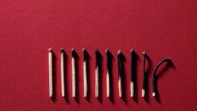 Μμένος matchsticks στο κόκκινο υπόβαθρο φιλμ μικρού μήκους