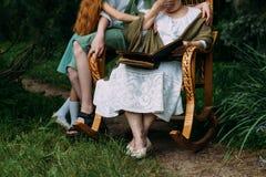 Μνήμες των ηλικιωμένων Γιαγιά επίσκεψης γιαγιά με τα εγγόνια της που κάθονται σε μια λικνίζοντας καρέκλα στον κήπο και το watchi Στοκ Φωτογραφίες