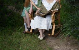 Μνήμες των ηλικιωμένων γιαγιά με τα εγγόνια της που κάθονται σε μια λικνίζοντας καρέκλα στον κήπο και που προσέχουν ένα παλαιό πν Στοκ Εικόνα