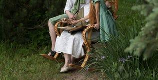 Μνήμες των ηλικιωμένων γιαγιά με τα εγγόνια της που κάθονται σε μια λικνίζοντας καρέκλα στον κήπο και που προσέχουν ένα παλαιό πν Στοκ εικόνες με δικαίωμα ελεύθερης χρήσης