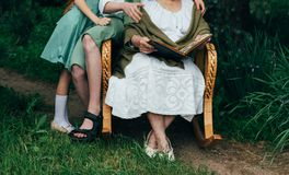 Μνήμες των ηλικιωμένων γιαγιά με τα εγγόνια της που κάθονται σε μια λικνίζοντας καρέκλα στον κήπο και που προσέχουν ένα παλαιό πν Στοκ φωτογραφία με δικαίωμα ελεύθερης χρήσης