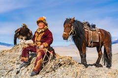 Μογγολικός χρυσός κυνηγός αετών με το άλογό του και καλά - ο εκπαιδευμένος χρυσός αετός κάθισε στην κορυφή του βουνού στοκ εικόνα με δικαίωμα ελεύθερης χρήσης
