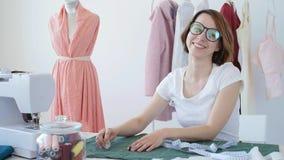 Μοδίστρα, ράφτης και έννοια μόδας - θηλυκός σχεδιαστής ιματισμού στον εργασιακό χώρο στο στούντιο απόθεμα βίντεο