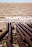 Μολυσμένη θάλασσα με τις σκουριασμένες σωληνώσεις στην ακτή Στοκ Εικόνα