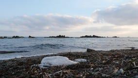 Μολυσμένη παραλία με το πλαστικό Ισχυρά κύματα που χτυπούν την παραλία και το ράντισμα φιλμ μικρού μήκους