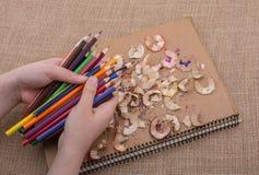 Μολύβια χρώματος εκμετάλλευσης χεριών πέρα από ένα σημειωματάριο Στοκ φωτογραφίες με δικαίωμα ελεύθερης χρήσης
