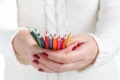 Μολύβια χρώματος εκμετάλλευσης χεριών στο λευκό Στοκ εικόνα με δικαίωμα ελεύθερης χρήσης