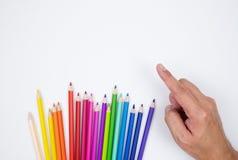 Μολύβια χρώματος και χέρι ατόμων που δείχνει το απομονωμένο ύφασμα άσπρο σε υπέροχο στοκ εικόνα με δικαίωμα ελεύθερης χρήσης
