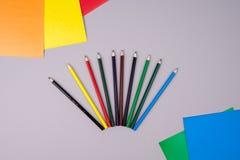 Μολύβια χρώματος και χρωματισμένο έγγραφο για το γκρίζο υπόβαθρο στοκ εικόνες