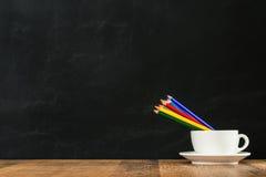 Μολύβια χρώματος ουράνιων τόξων στο άσπρο φλυτζάνι καφέ Στοκ φωτογραφία με δικαίωμα ελεύθερης χρήσης
