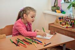 Μολύβια χρώματος σχεδίων κοριτσιών στην τάξη παιδικών σταθμών, τον παιδικό σταθμό και την έννοια εκπαίδευσης παιδιών στοκ εικόνα