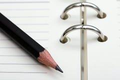 Μολύβι στο σημειωματάριο Στοκ Εικόνες