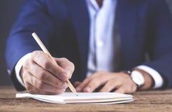 Μολύβι χεριών ατόμων με το σημειωματάριο στο ξύλινο γραφείο στοκ εικόνες