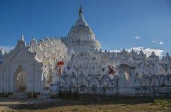 Μοναχοί με τα κόκκινα παραδοσιακά κοστούμια και κόκκινη ομπρέλα στο βουδιστικό ναό στοκ εικόνες