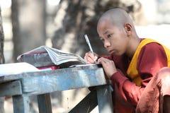 Μοναχός που γράφει σε ένα βιβλίο Στοκ Εικόνες