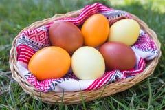 Μοναδικά χρωματισμένα χέρι αυγά Πάσχας στο καλάθι στη χλόη Στοκ Φωτογραφίες
