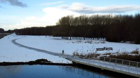 Μονοπάτι που οδηγεί πέρα από τη γέφυρα στο δάσος που καλύπτεται στο χιόνι και τον πάγο Στοκ Εικόνα