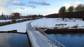 Μονοπάτι που οδηγεί πέρα από το κανάλι στο δάσος που καλύπτεται στο χιόνι και τον πάγο Στοκ Εικόνες