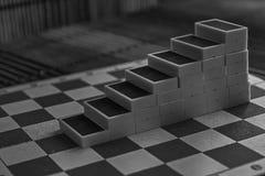 Μονοχρωματική πυραμίδα των κομματιών ντόμινο στο καφετί ξύλινο επιτραπέζιο υπόβαθρο μπαμπού Στοκ Φωτογραφία