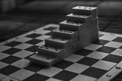Μονοχρωματική πυραμίδα των κομματιών ντόμινο στο καφετί ξύλινο επιτραπέζιο υπόβαθρο μπαμπού Στοκ Εικόνες