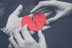 Μονοχρωματική φωτογραφία των αρσενικών και θηλυκών χεριών που επισκευάζουν μια σπασμένη καρδιά Έννοια διαζυγίου Έννοια αγάπης στοκ εικόνα
