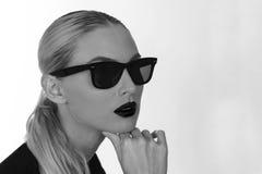 Μονοχρωματικός πυροβολισμός ενός κοριτσιού με τα γυαλιά ηλίου Στοκ Φωτογραφία